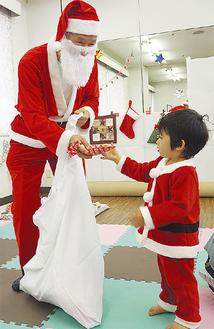 サンタからお菓子を受け取る子ども