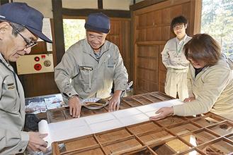のりを塗った桟に、慎重に障子紙を貼る参加者たち