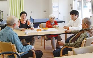 光溢れる施設で、談笑しながら会話も弾む利用者と施設長ら