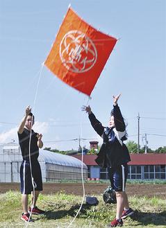 校章を描いた凧などが南風に乗って上空へ