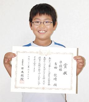 賞状を持ち笑顔の吉田君