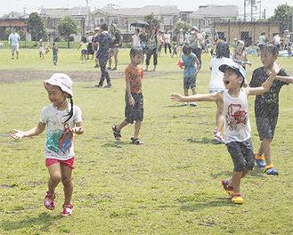 芝生を駆け回り、水浴びを楽しむ子どもたち