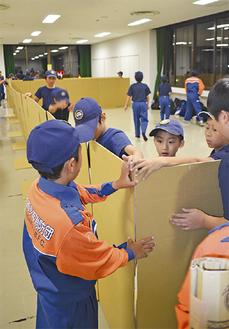 段ボールで避難所の仕切りを作る団員たち