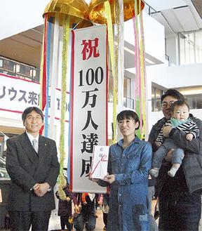 くす玉を割り記念撮影をする大木市長(左)と甘粕さん一家