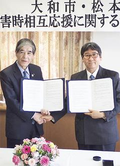 協定書を手に握手する両市長