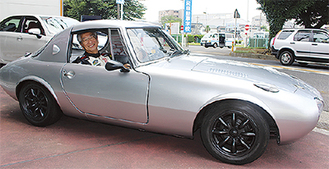 往年のスポーツカー「トヨタスポーツ800」に乗りこむ横田社長