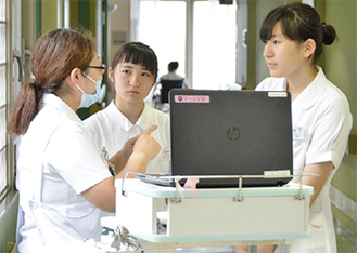 真剣な表情で看護師の説明を聞く生徒たち