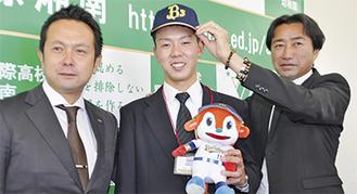 中川アマチュアスカウトグループ長(右)から帽子を被せてもらう本田投手。左は由田スカウト