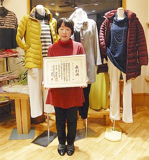 服の前で表彰状を持つ鈴木静子さん