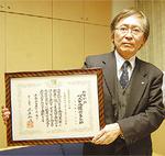 表彰状を持つ古谷田理事長