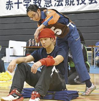 三角巾で傷の手当てを行う参加者