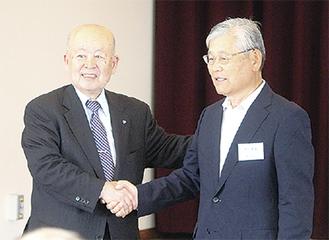 竹下会長(左)と伴新会長が握手