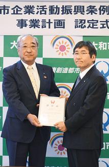 認定書を受け取る長谷川社長(左)と、大木市長