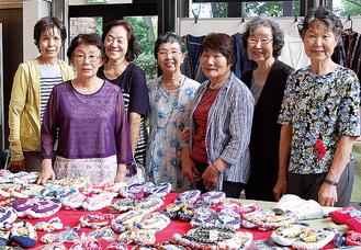 作品を前に笑顔の会員と代表の鈴木さん(中央)