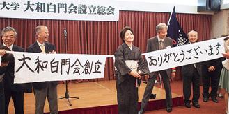副会長らと謝辞を述べる岡田会長(中央)