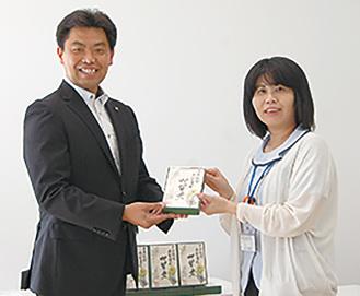 カルタを手渡す石井さん(左)と來嶋館長(左)