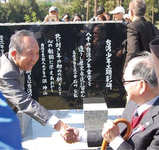 顕彰碑の前で固い握手を交わす、石川公弘さん(左)と李雪峰さん。顕彰碑には、石川さんらが創作した3つの句が記されている=芹沢公園(座間市栗原)
