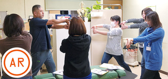 腰痛改善のためのポーズをとる参加者