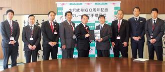市長にオリジナルフレーム切手を手渡す清水支社長(中央左)