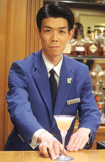 東京都知事賞のブルージャケットを着てカクテルを提供する鮎川さん