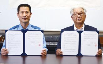 協定書を手にする宮東会頭(右)と千葉署長