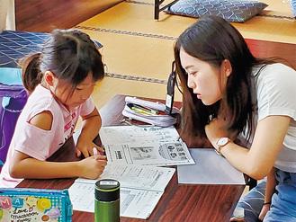 机に向かう児童と講師の大学生