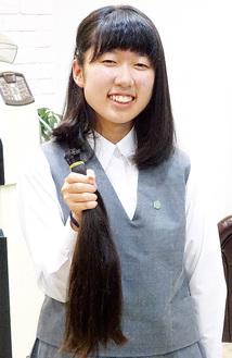 自らのカットした髪を手にする桃佳さん