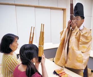 装束に身を包んだ会員が雅楽器を手ほどき