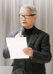 中村氏の写真を見つめながら弔辞を読む斎藤さん