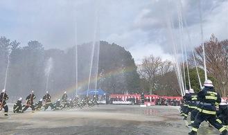 一斉放水をする団員の間には虹がかかった