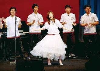 揃いの衣装で舞台に立つ森口博子さん(中央)と高校生合唱団