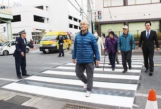 信号機が点灯した横断歩道を渡る善光明自治会の人々