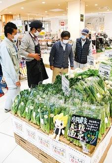売り場に並ぶ旬の野菜と関係者=4月30日撮影