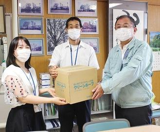 山内校長、平野さんに手袋を手渡す酒井代表(右)