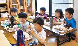 昼食を食べる児童