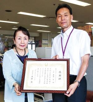寄付の感謝状を受け取る岩本会長(左)と健康福祉部の目代部長