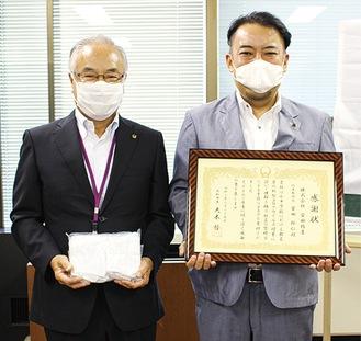 安田社長(右)と寄贈された手作りマスクを手にする柿本教育長