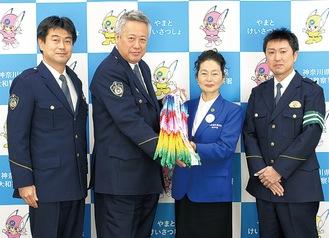 千羽鶴を寄贈した石原会長(中央右)と加藤署長(中央左)と署員ら