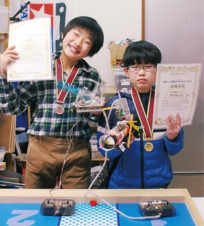 メダルをかけ、自作と賞状と持ち笑顔の伊地知君(右)と岸君