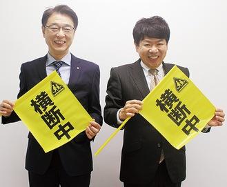 横断旗を持つ新村会長(左)と吉原一彦副会長