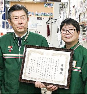 感謝状を手にするオーナーの土田さんと男性従業員