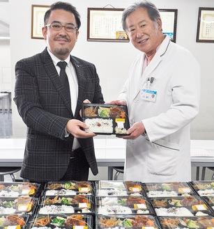 安田代表(左)が吉田院長に弁当を手渡した