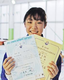 記録証と表彰状2枚を手に笑顔を見せる
