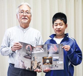 資料集を手にする上田さん(左)と孫の平川唯斗君