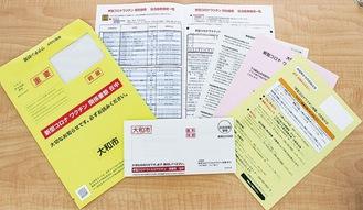 白抜き文字で「新型コロナワクチン関係書類在中」と記載された黄色い専用封筒。視覚障害者のための2次元コードや外国人市民のための外国語表記もなされている