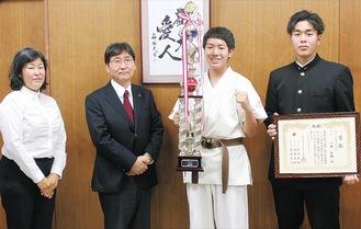 トロフィーを片手に大木市長の隣で微笑む小林佑輔さん左端は佐野代表、右端は佑輔さんの兄の良輔さん