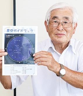 出来上がった「星空ガイドブック」を手にする木村さん