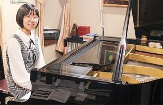 ピアノの前で笑顔の西堀さん