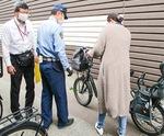 自転車の運転手に注意を促す警察官