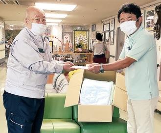 寄付金を手渡す竹下事務局長(左)と天野施設長